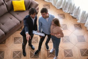 Realtor with house plan showing young couple around property for sale, above view